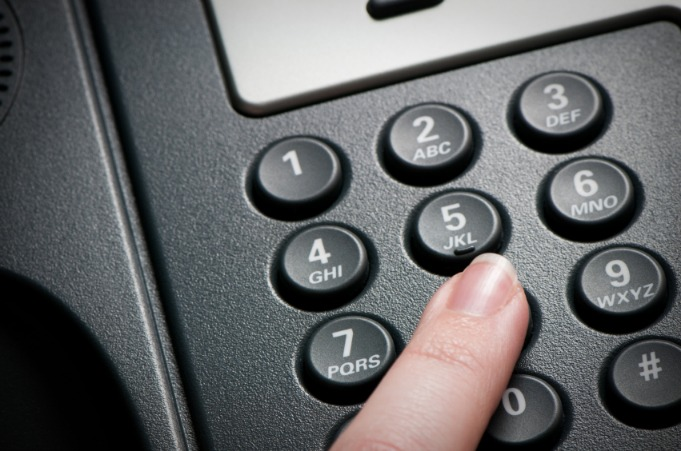 woman pressing a VoIP conference call telephone
